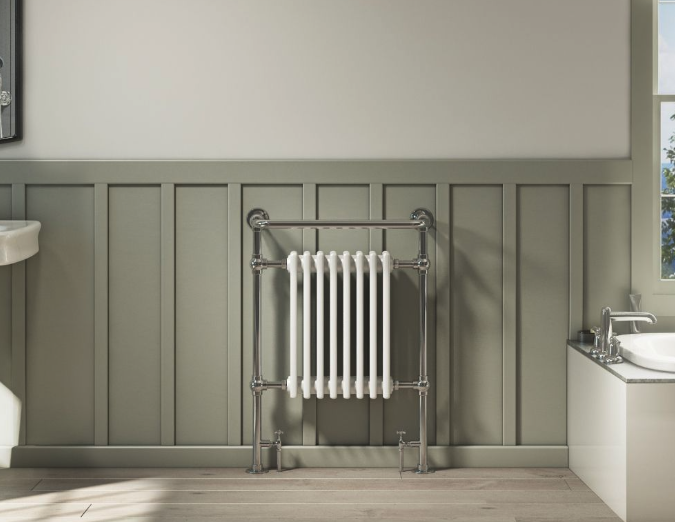 Traditional white towel rail on an olive coloured wall with a bath to the right