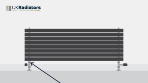 dark grey horizontal radiator with bottom connecitons and an arrow pointing the the valve